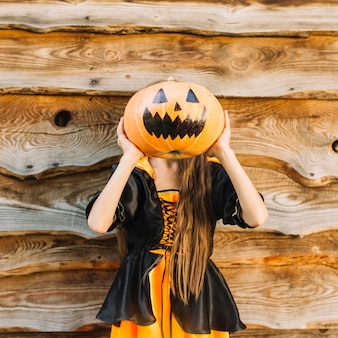 Girl in witch costume closing face by pumpkin