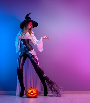 The girl in a witch costume for halloween with a broom and a pumpkin in neon light