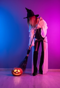 A girl in a witch costume for halloween with a broom and a pumpkin in neon light