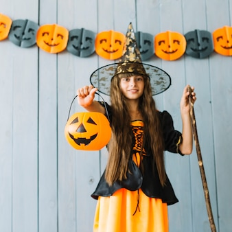 Girl in witch costume holding halloween basket