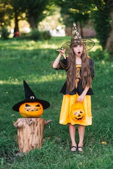 Girl in witch costume showing reach out hand near pumpkin
