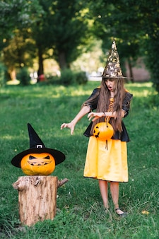 Girl in witch costume showing reach out hands on pumpkin