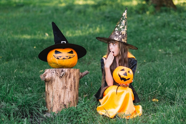 Girl in witch costume showing surprise near pumpkin
