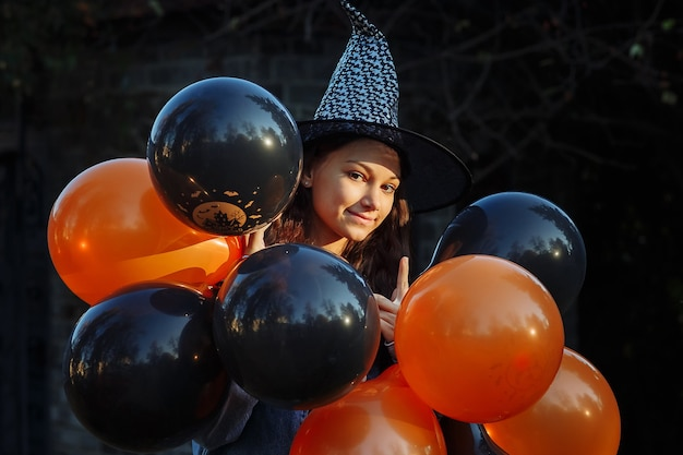 A girl in a witch hat with black and orange balloons in her hands is getting ready for halloween