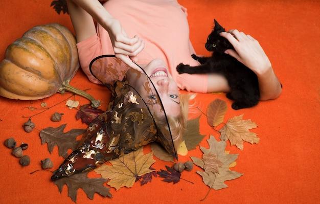 Девушка-ведьма играет с черным котенком хэллоуинская ведьма в черной шляпе. женщина позирует с тыквой. фонарь с тыквенной головкой. кошелек или жизнь.