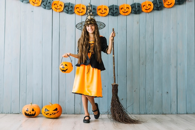 Girl in witch suit holding halloween basket and broom