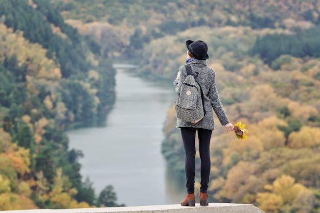 Девушка с рюкзаком и шляпой стоит на холме. река и лес внизу. вид сзади