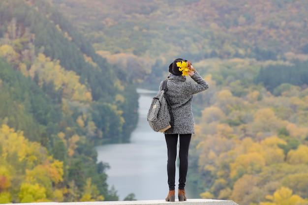 Девушка с рюкзаком и шляпой стоит на холме. река и горы внизу. вид сзади