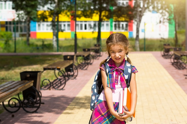 学校の近くにバックパックと本のスタックを持つ少女。学校に戻ると、子供は疲れていて重い教科書です。教育、小学校の授業、学年の初め、9月1日