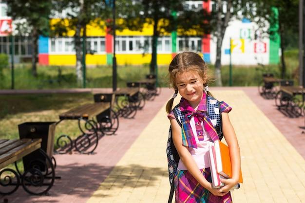 学校の近くにバックパックと本のスタックを持つ少女。学校に戻る、