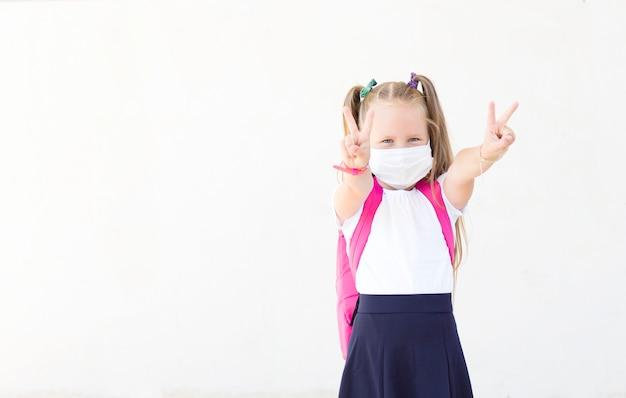マスクのバックパックを持つ少女