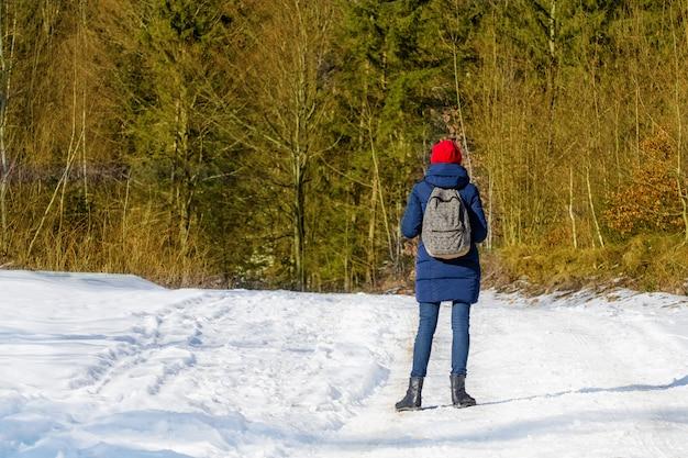 雪に覆われた森の中に立っている赤い帽子のバックパックを持つ少女。冬の晴れた日。
