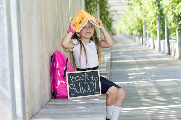 公園でバックパックを持つ少女。学校の最初の日