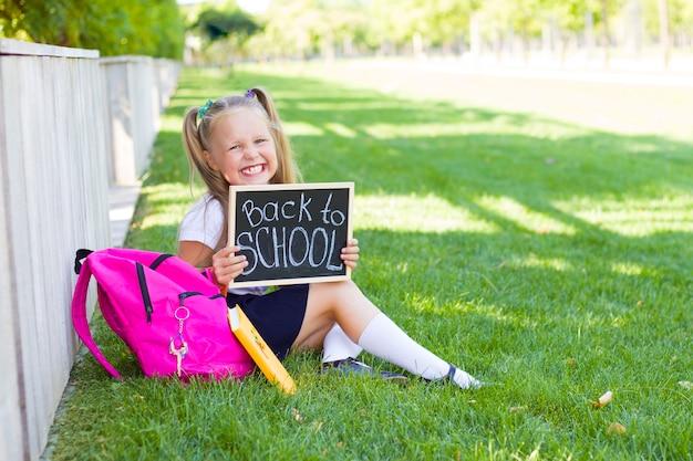 バックパックを持つ少女は芝生の上に座っています。学校の最初の日