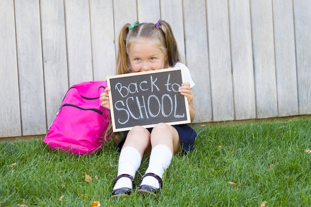 バックパックを持つ少女は芝生に座っています。