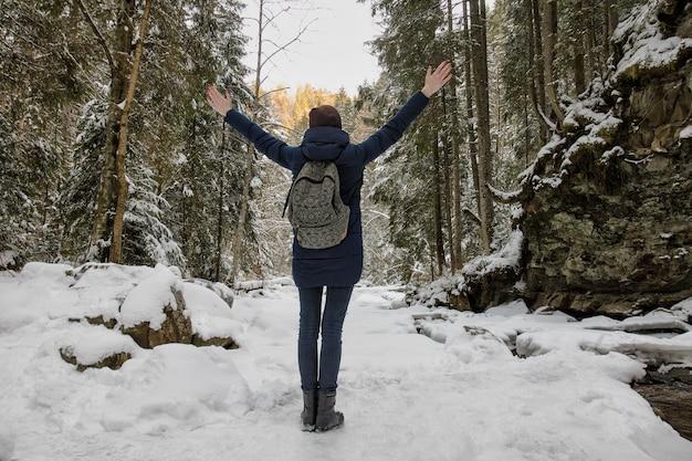 雪に覆われた森で腕を上げて立っているバックパックを持つ少女
