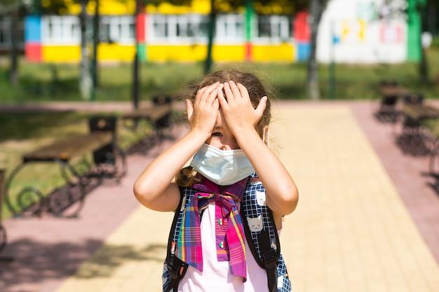 授業が終わった後、学校の近くでバックパックを背負った少女は、医療用マスクを脱いで、不幸で、疲れていて、頭痛がします。彼は両手で頭を抱えており、酸素が不足しています。コロナウイルス、セキュリティ対策