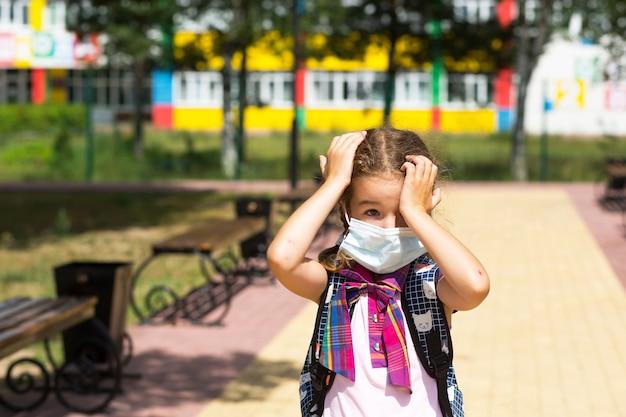 방과 후에 학교 근처에 배낭을 메고 있는 소녀는 의료용 마스크를 벗고 불행하고 피곤하고 두통이 있습니다. 그는 손으로 머리를 잡고 산소가 부족합니다. 코로나바이러스, 보안 조치