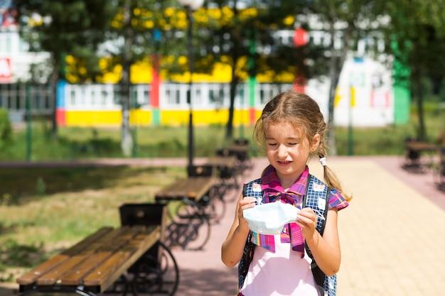 수업 후 학교 근처에서 배낭을 메고 의료 마스크를 벗고 불행한 소녀