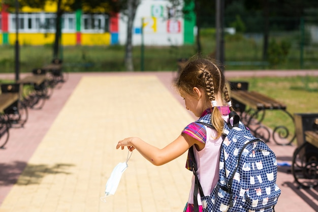방과 후 학교 근처에 배낭을 메고 의료 마스크를 벗고 불행하고 피곤한 소녀. 코로나바이러스 감염, 보안 조치, 예방 조치.