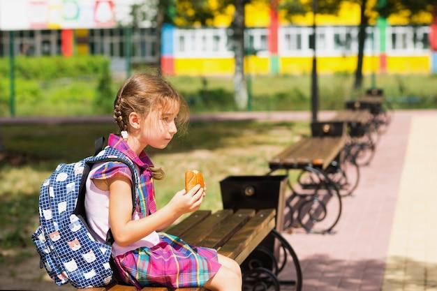 Девушка с рюкзаком сидит на скамейке и ест пирог возле школы. быстрый перекус булочкой, нездоровая еда, обед из дома. обратно в школу. образование, начальные классы, 1 сентября