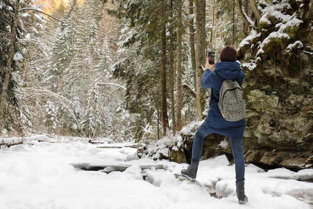 雪に覆われた針葉樹林にバックパックに立って、スマートフォンで写真を撮る女の子
