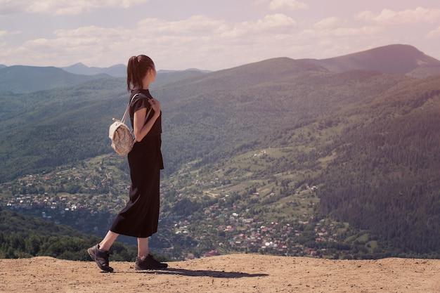 Девушка с рюкзаком стоит на холме и любуется видом. солнечный день