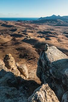 バックパックを背負った少女が山の崖の端に立って、夕日の谷を後ろから眺めています。