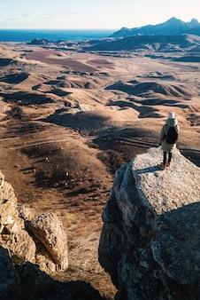 배낭을 가진 소녀는 산에서 절벽의 가장자리에 서