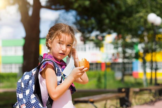 배낭을 메고 있는 소녀는 의료용 마스크를 벗고 학교 근처에서 파이를 먹고 있습니다. 롤빵으로 간단한 간식, 건강에 해로운 음식, 집에서 점심. 학교로 돌아가다. 교육, 초등학교 수업, 9월 1일