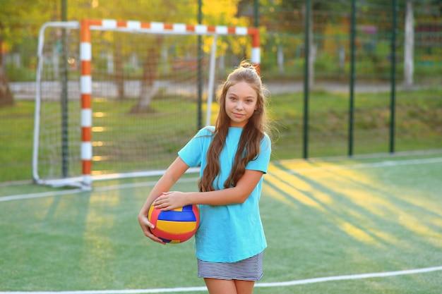 サッカーのフィールドで彼の手にボールを持つ少女。