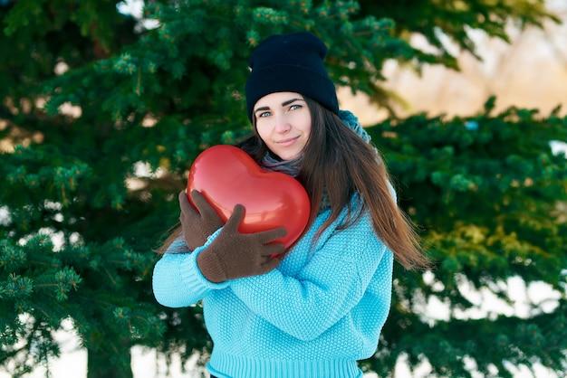 Девушка с воздушным шаром в форме сердца в руках. день святого валентина