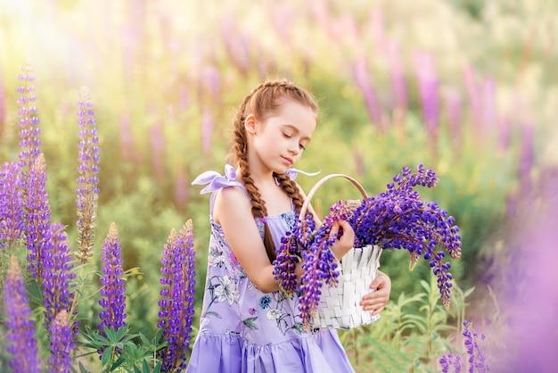 紫色の花のバスケットを持つ少女。自然の中の子供。花が畑の少女