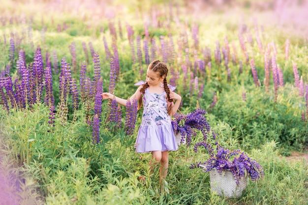 紫色の花のバスケットを持つ少女。花のフィールドの子
