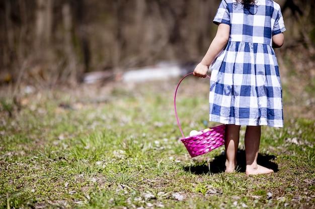 野原の緑の草の上にカラフルなイースターエッグのバスケットを持つ少女