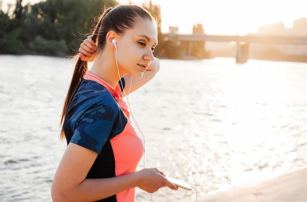 川岸でジョギングした後、美しいロングテールの女の子が音楽を聴く