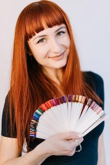 Девушка с красивым маникюром, держа в руках образцы маникюра. портрет женщины с рыжими волосами.