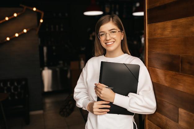 아름다운 미소를 가진 소녀는 그녀의 손에 노트북을 보유하고 격리 된 배경