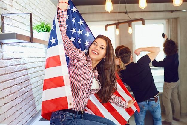 실내 미국 국기와 함께 아름다운 미소를 가진 소녀