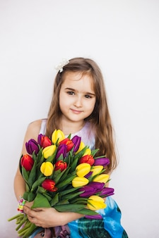 チューリップの大きな花束を持つ少女。春の花を持つ少女。