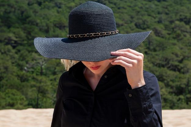 Девушка в большой шляпе на природе