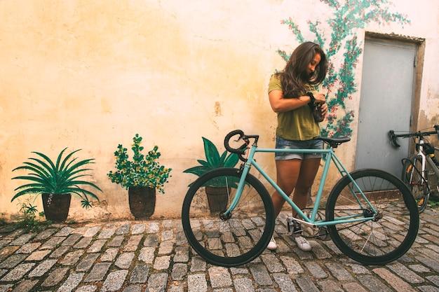 壁の前の石畳の通りに自転車を持っている女の子コピースペースライフスタイルのコンセプト