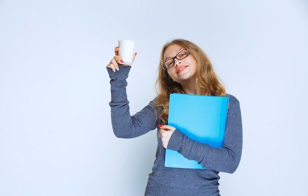일회용 커피 컵을 들고 파란색 폴더와 소녀.
