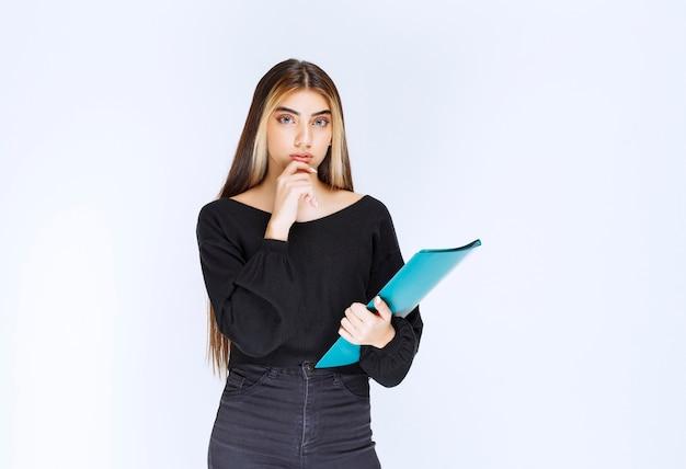 青いフォルダーを持つ女の子は混乱して思慮深く見えます。高品質の写真