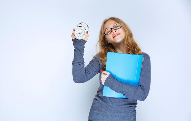 그녀의 알람 시계를 보여주는 파란색 폴더와 소녀.