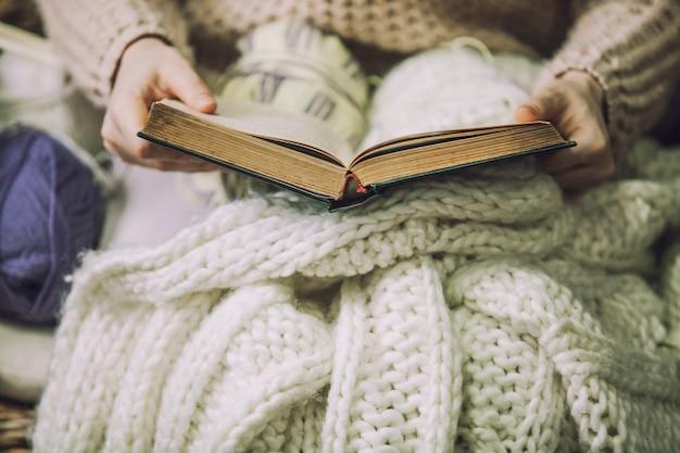 손에 책을 들고 있는 소녀는 손으로 뜨개질을 하기 위해 엉킨 담요로 싸여 있다
