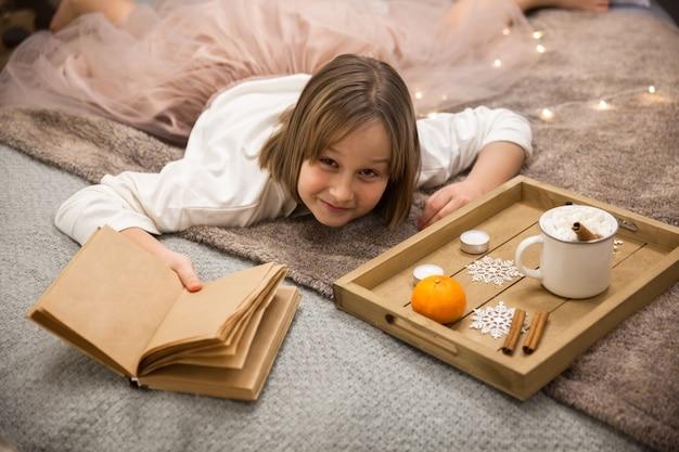 ベッドに横たわっている本を持つ少女、ベッドで朝食