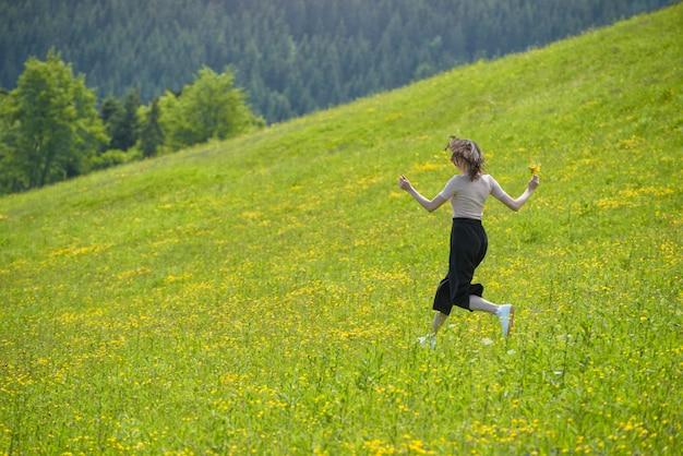 꽃다발 소녀 꽃 초원에서 실행 중입니다. 화창한 여름날