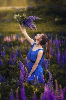 Девушка с букетом цветов, зеленый луг, фиолетовые и розовые цветы