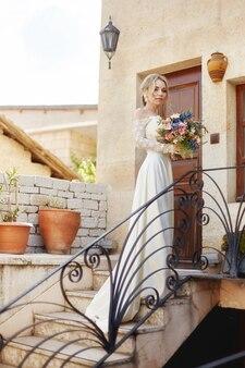Девушка с букетом цветов в руках ждет любимого мужчину возле дома. идеальная прическа и красивое длинное платье, вьющиеся волосы. история о любви